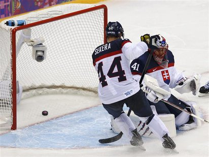 Slovakia's goalie Jaroslav Halak and teammate Andrej Sekera let in a goal by Slovenia's Rok Ticar, not seen, during the third period of thei