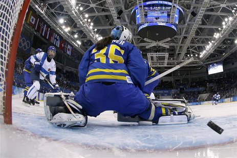 Finland's Emma Nuutinen (L) shoots past Sweden's goalie Valentina Wallner to score during the third period of their women's ice hockey playo