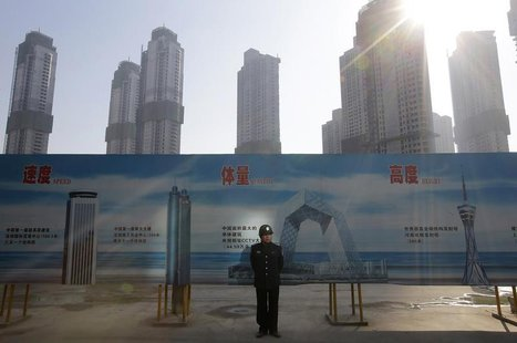 A security guard stands next to an advertising board in front of a residential compound under construction in Wuhan, Hubei province January
