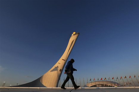 A workman walks on the cauldron at sunrise at the Olympic Park during the 2014 Sochi Winter Olympics, February 15, 2014. REUTERS/Gary Hersho