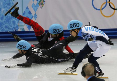 Canada's Charles Hamelin (back) and Eduardo Alvarez of the U.S. (front) fall as Russia's Victor An (R) skates past during the men's 1,000 me
