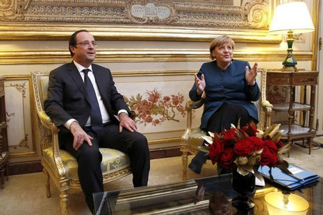 French President Francois Hollande and German Chancellor Angela Merkel (R) meet in President's office prior to a dinner at the Elysee Palace