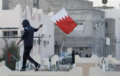 An anti-government protester waves a Bahraini flag in the village of Jidhafs, west of Manama, February 14, 2014. REUTERS/Hamad I Mohammed