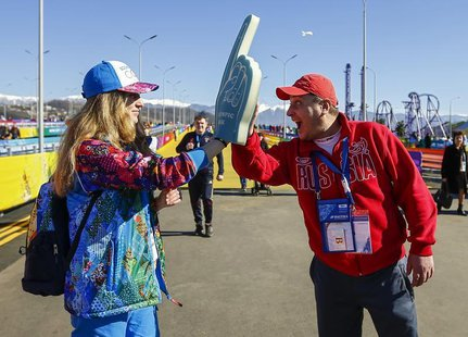 A fan (R) greets Yuliya Udalykh, a volunteer from the Urals city of Yekaterinburg, at the entrance to the Olympic Park during the Sochi 2014