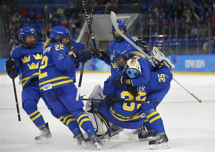Sweden's women's ice hockey players celebrate after defeating Finland in their women's ice hockey playoffs quarter-final game at the Sochi 2