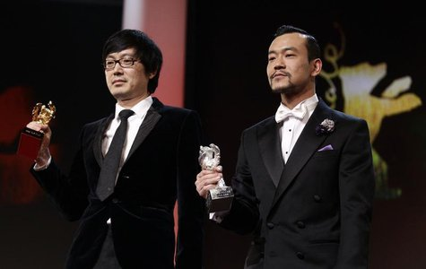 "Diao Yinan (L) director of ""Bai Ri Yan Huo"" (Black Coal, Thin Ice) poses with his Golden Bear for Best Film next to actor Liao Fan (R) who p"