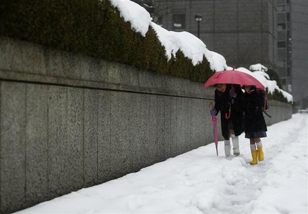 School children share an umbrella on a street covered by snow near the Bank of Japan building in Tokyo February 15, 2014. REUTERS/Yuya Shino