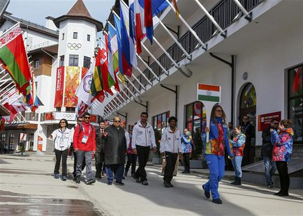 Members of India's national athletes team walk to attend the welcoming ceremony for the team in the Olympic athlete's village, which stands