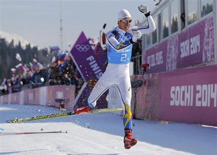 Sweden's Marcus Hellner celebrates after crossing the finish line during the men's cross-country 4 x 10km relay event at the 2014 Sochi Wint
