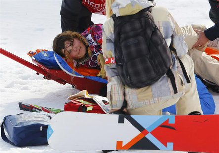 Jacqueline Hernandez of the U.S. reacts on a stretcher after crashing during the women's snowboard cross qualification round at the 2014 Soc