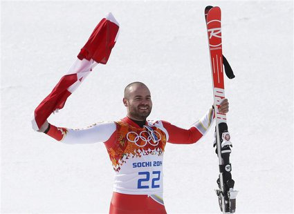 Canada's third-placed Jan Hudec celebrates with a flag during a flower ceremony after the men's alpine skiing Super-G competition during the