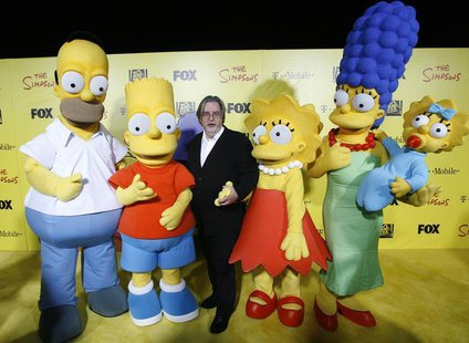 Matt Groening (C), creator of The Simpsons, poses with characters from the show (L-R) Homer, Bart, Lisa, Marge and Maggie at the 20th annive