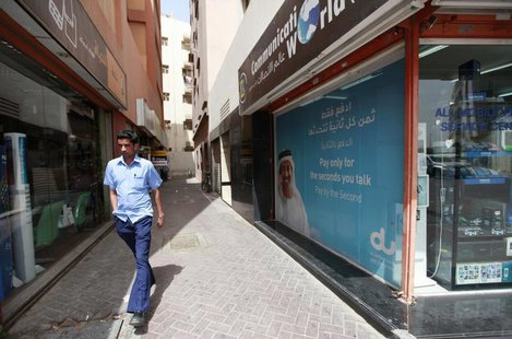 A man walks past a Du telecommunications advertisement in Deira in Dubai March 12, 2012. REUTERS/Jumana El Heloueh