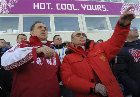 Russian President Vladimir Putin (C) and Sports Minister Vitali Mutko (L) watch the cross country skiing men's relay during the Sochi 2014 O