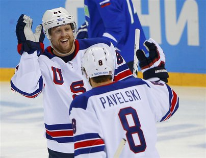 Team USA's Phil Kessel is congratulated by teammate Joe Pavelski after scoring on Slovenia during the first period of their men's preliminar