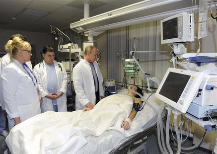 Russia's President Vladimir Putin (R) visits Russian Olympic skicross racer Maria Komissarova at a hospital in Sochi, February 15, 2014. REU