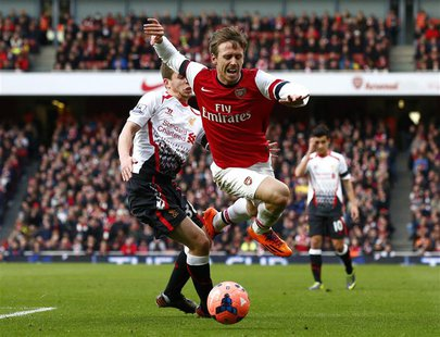 Arsenal's Nacho Monreal (R) is fouled by Liverpool's Jon Flanagan during their English FA Cup fifth round soccer match at the Emirates stadi