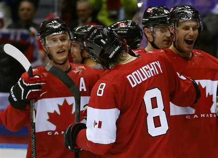 Canada's Drew Doughty (8) celebrates his game winning overtime goal against Finland with teammates during their men's preliminary round ice