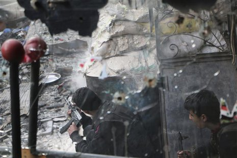 A Free Syrian Army fighter, seen through a mirror riddled with bullets, fires his weapon towards forces loyal to Syria's President Bashar al