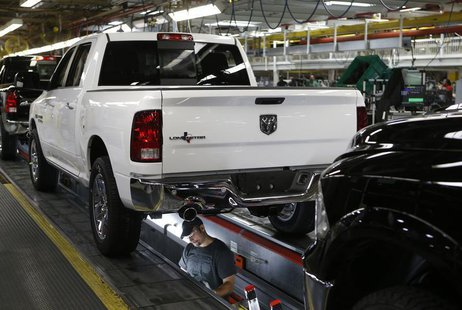 Chrysler Group assembly staff works below a 2014 Dodge Ram pickup truck at the Warren Assembly Plant in Warren, Michigan December 11, 2013.