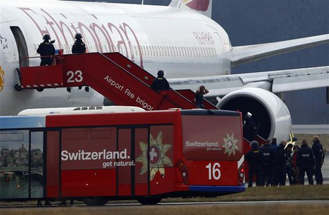 A passenger (4th L) climbs down an airplane ladder with his hands on his head as police officers stand around hijacked Ethiopian Airlines fl