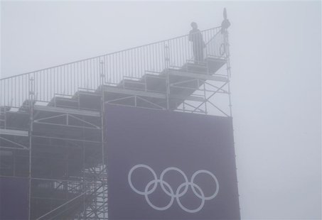 A person looks on from a spectator stand amidst fog during a delayed start for the men's snowboard cross competition at the 2014 Sochi Winte