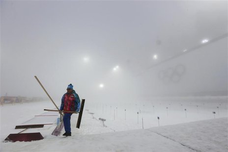 A worker walks past the track before the start of the men's biathlon 15km mass start event at the Sochi 2014 Winter Olympic Games in Rosa Kh
