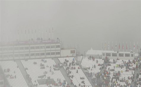 Spectators stand in the stands at the venue for the men's snowboard cross competition at the 2014 Sochi Winter Olympic Games in Rosa Khutor