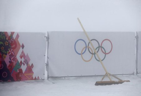 A broom is seen leant against a barrier bearing the Olympic rings as thick fog surrounds the Laura Cross Country Ski and Biathlon Center at