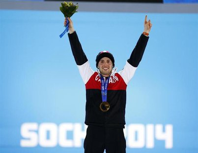 Gold medallist Alex Bilodeau of Canada poses during the medals ceremony for the men's freestyle skiing moguls competition at the 2014 Sochi