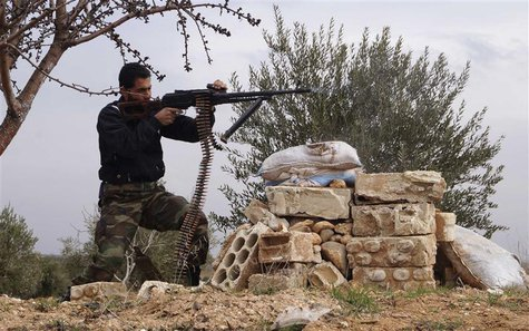 A Free Syrian Army fighter takes a position as he fires his weapon during clashes with forces loyal to Syria's President Bashar al-Assad in