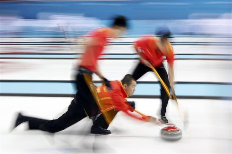 China's skip Liu Rui (C) delivers a shot during their men's curling round robin game against Britain at the Ice Cube Curling Center during t
