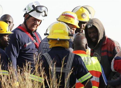 A suspected illegal miner talks to officials after being rescued from an abandoned gold shaft in Benoni, east of Johannesburg, February 16,