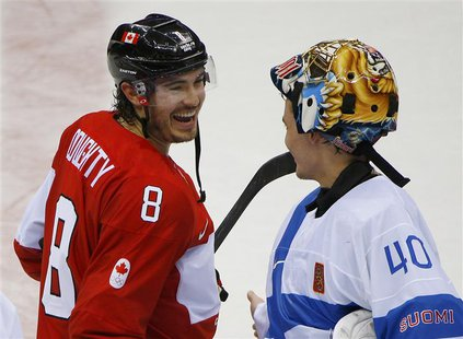 Canada's Drew Doughty laughs with Finland's goalie Tuukka Rask after Canada defeated Finland in overtime in their men's preliminary round ic