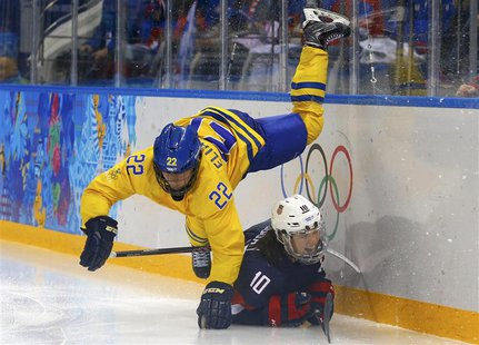 Sweden's Emma Eliasson falls over Team USA's Meghan Duggan during the third period of their women's semi-final ice hockey game at the 2014 S