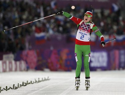Darya Domracheva of Belarus celebrates as she approaches the finish line to win the women's biathlon 12.5km mass start event at the Sochi 20