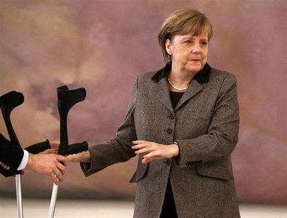 An aide take the crutches of German Chancellor Angela Merkel as she attends the appointment ceremony of the new Agriculture Minister Christi
