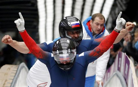 Russia's pilot Alexander Zubkov and Alexey Voevoda gesture after completing the final run of the men's two-man bobsleigh competition at the