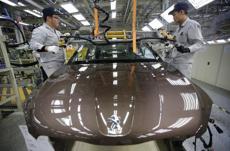 Employees work at a production line of a Dongfeng Peugeot Citroen Automobile factory in Wuhan, Hubei province, February 13, 2014. REUTERS/St
