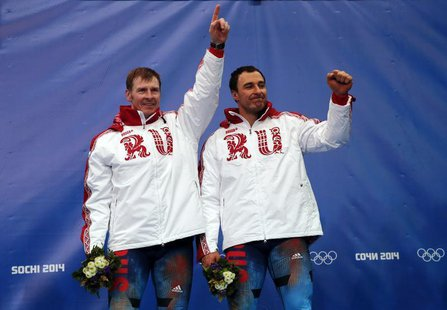 Russia's pilot Alexander Zubkov (L) and Alexey Voevoda celebrate on the podium at the flower ceremony after winning the men's two-man bobsle