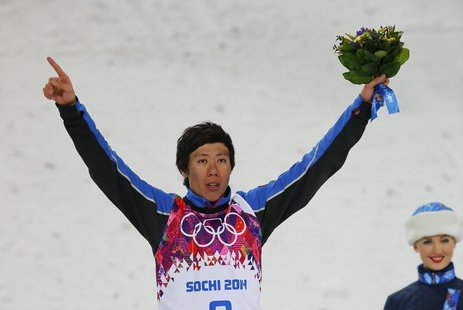 China's third placed Jia Zongyang celebrates on podium after the men's freestyle skiing aerials finals at the 2014 Sochi Winter Olympic Game
