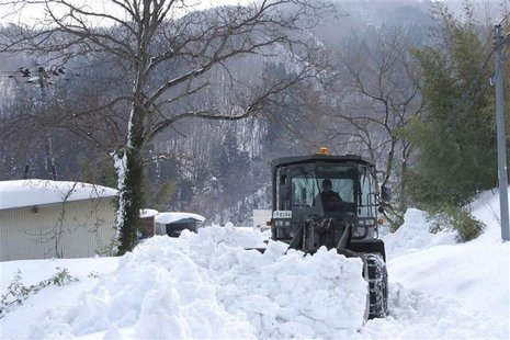 A loader of the Japan Ground Self-Defence Force removes snow covering a public road in Marumori town, Miyagi prefecture, in this handout pic
