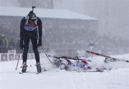 Norway's Emil Hegle Svendsen celebrates as France's Martin Fourcade (R) lunges and falls, as they cross the finish line during the men's bia