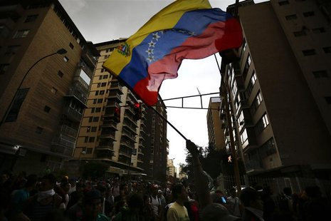 An opposition supporter waves a national flag during a protest against President Nicolas Maduro's government in Caracas February 17, 2014. R
