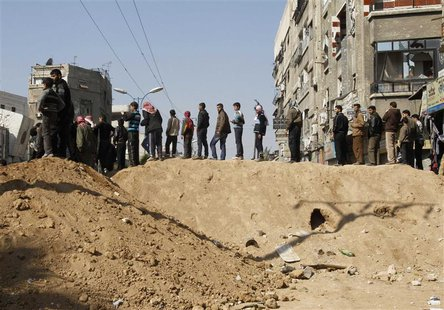 Syrian civilians are seen in Babila town, southeast Damascus February 17, 2014, after a local ceasefire agreement was reached. REUTERS/Khale