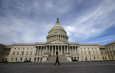 A lone worker passes by the U.S. Capitol Building in Washington, October 8, 2013. REUTERS/Jason Reed