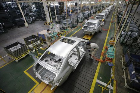 Employees assemble cars at a production line of Dongfeng Peugeot Citroen Automobile factory in Wuhan, Hubei province, February 13, 2014. REU