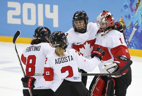 Canada's goalie Shannon Szabados (R) is congratulated by teammates Jocelyne Larocque (C), Laura Fortino (8) and Meghan Agosta-Marciano (2) a