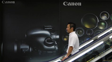 A man takes a downward escalator in front of an advertisement of Canon digital cameras at an electronics retail store in Tokyo July 24, 2013