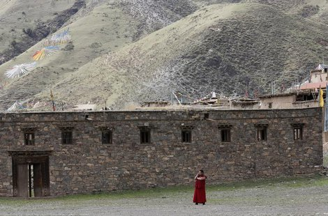 A Tibetan monk uses a mobile phone near the Dzamthang Jonang monastery in Barma township May 16, 2013. REUTERS/Kim Kyung-Hoon
